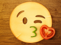 A kissing face emoji made from a piece of cheese (for the face), a piece of green pepper (for the mouth) and half a cherry tomato (for the heart/kiss).